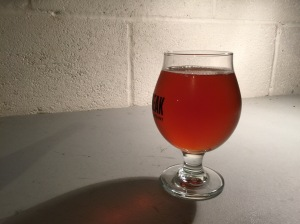 An IPA beer poured into a snifter glass.