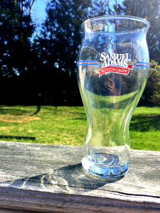 Samuel Adams Brewing developed this glass to deliver the optimal drinking experience for their beers. The tapered top allows some aroma to be trapped toward the top of the glass, while the bottom inside is finely etched by lasers to reduce surface tension and generate more bubbles.